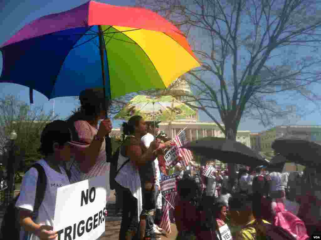 Immigration activists take refuge from the sun under umbrellas while rallying for Congress to create a pathway to citizenship for the undocumented immigrants in the U.S. Washington, DC, Wednesday, April 10, 2013. (Photo by Kate Woodsome)