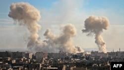 دود غلیط پس از بمباران هوایی در منطقۀ غوطه در حومۀ دمشق به هوا بلند است.