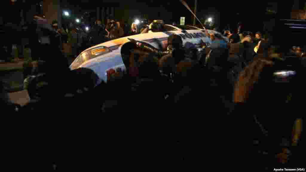 In a second night of violence following a grand jury's decision not to indict a white police officer in the shooting death of a black teenager, protesters attack and turn over a police car outside Ferguson City Hall, in Ferguson, Missouri, Nov. 25, 2014.