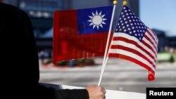 Seorang demonstran membawa bendera Taiwan dan AS saat Presiden Taiwan Tsai Ing-wen transit di Burlingame, California, tahun lalu dari perjalanan ke Amerika Latin. (Foto: ilustrasi).