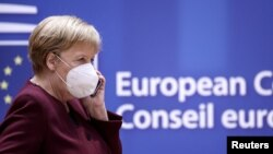 Germany's Chancellor Angela Merkel, wearing a face mask, speaks on the phone as she attends a two-day face-to-face EU summit, in Brussels, Belgium October 16, 2020. Kenzo Tribouillard/Pool via REUTERS