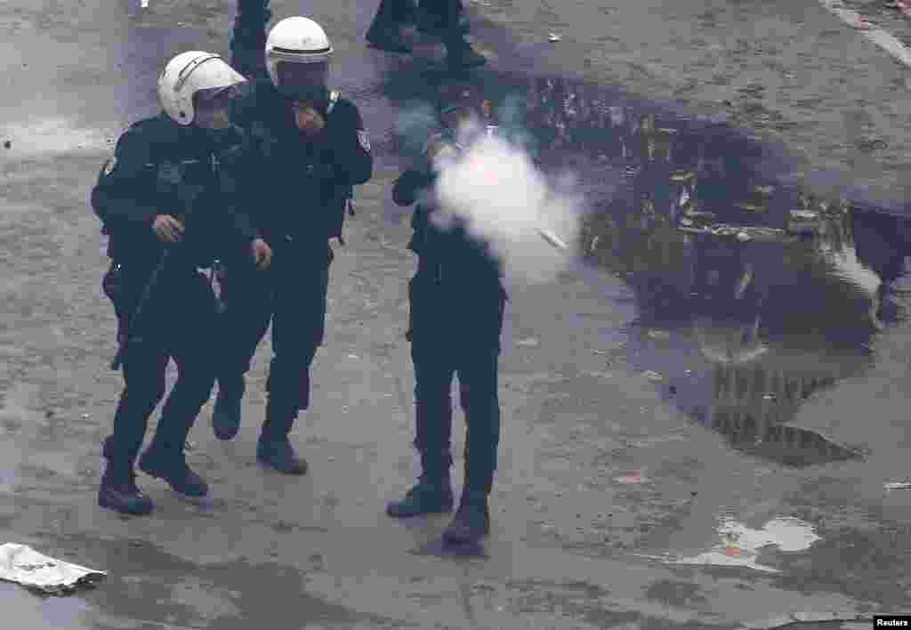 A riot police officer fires tear gas to push back protesters during a May Day demonstration in Istanbul, Turkey.