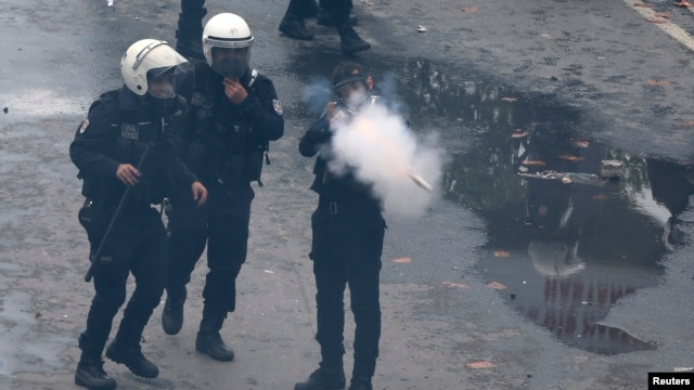 A riot police officer fires tear gas to push back protesters during a May Day demonstration in Istanbul, May 1, 2014.