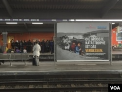 """Migrants await their fate at Freilassing's train station in Germany near a billboard by charity groups urging Germans to support refugees. It reads: """"The biggest catastrophe is forgetting. 12 million people from Syria and Iraq are fleeing. We must support them."""" (L. Ramirez/VOA)"""