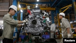 FILE - Men work with an engine at automaker Ford Vietnam's factory in Vietnam's northern Hai Duong province, outside Hanoi June 27, 2014.