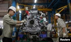 FILE - Men work with an engine at automaker Ford Vietnam's factory in Vietnam's northern Hai Duong province, outside Hanoi, Vietnam, June 27, 2014.