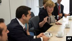 Perdana Menteri Yunani Alexis Tsipras (kiri) dan Kanselir Jerman Angela Merkel pada pertemuan Presiden Komisi Eropa Jean-Claude Juncker dan Presiden Perancis Francois Hollande sebelum pertemuan para pemimpin zona euro di Brussels, Selasa (7/7).