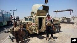 Các phần tử nổi dậy đứng cạnh xe Humvee chiếm được của quân đội Iraq ở phía bắc thủ đô Baghdad.