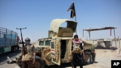 Các phần tử chủ chiến đứng cạnh chiếc xe quân sự Humvee chiếm giữ từ quân đội Iraq tại một trạm kiểm soát bên ngoài nhà máy lọc dầu Beiji, Iraq 19/6/2014.