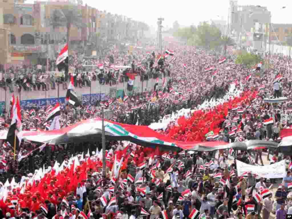 Sadr supporters wave Iraqi national flags as they march on a street during a protest in Baghdad April 9, 2011. (Reuters)