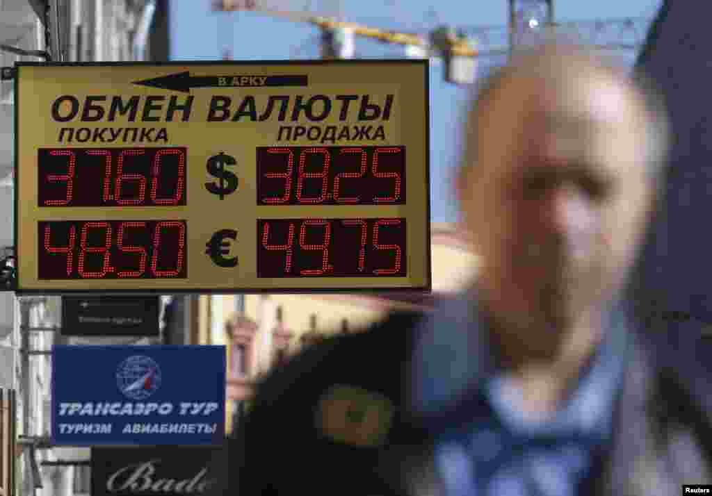 The Russian rouble hit new historic lows against the dollar on Monday, falling to 38 roubles per dollar. Here, a man walks past a board displaying currency exchange rates in Moscow, Sept. 15, 2014.