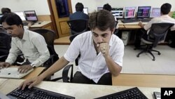 A stock broker watches the Bombay Stock Exchange (BSE) index on his trading terminal in Mumbai, India, Aug. 8, 2011.