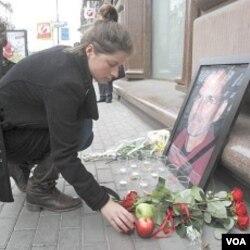 Seorang wanita Rusia meletakkan buah apel di dekat foto Steve Jobs di luar gerai Apple di Moskow (6/10).