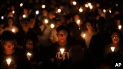 Tens of thousands of people attend an annual candlelight vigil at Hong Kong's Victoria Park, Monday, June 4, 2018.