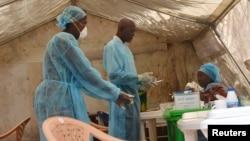 Ma'aikatan kiwon lafiya zasu binne gawar waniw anda cutar Ebola ta kashe a Kenema, kasar Saliyo, 25 Yuni, 2014.