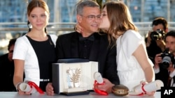 Director Abdellatif Kechiche, center, actors Lea Seydoux, left, and Adele Exarchopoulos pose with the Palme d'Or award for the film La Vie D'Adele after an awards ceremony at the 66th international film festival, in Cannes, southern France, Sunday, May 26