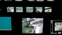 FILE - Screens for surveillance cameras show various points along the border between Nogales, Mexico, and Nogales, Arizona, in a U.S. Border Patrol station in Nogales, Arizona.
