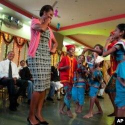 Le président Obama regarde la première dame Michelle Obama et des élèves d'un collège danser à l'occasion du festival de Diwali à New Dehli
