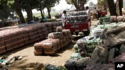 FIle - South Sudanese men inspect crates of soft drinks that were unloaded at the port in Juba, Southern Sudan.