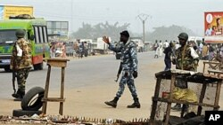 FDS soldiers, loyal to incumbent president Laurent Gbagbo, man a security checkpoint at the entrance of the Abobo district of Abidjan, 13 Jan 2011