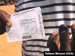 A voter shows her voter card and her finger marked with indelible ink after voting at the school Gobongo the 4th arrondissement, Bangui, Dec. 30, 2015.