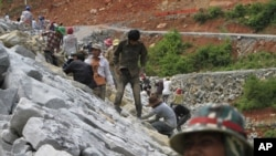Local workers adjust stones at a dam construction site, file photo.
