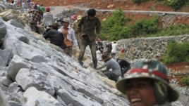 In this Oct. 6, 2012 photo, local workers adjust stones at another dam construction site by China National Heavy Machinery Corporation on the Tatay River in Koh Kong province, some 210 kilometers (130 miles) west of Phnom Penh, Cambodia.