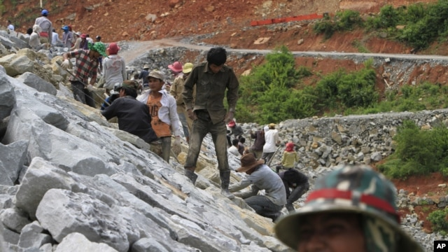 Local workers adjust stones at a dam construction site by China National Heavy Machinery Corporation on the Tatay River in Koh Kong province, some 210 kilometers (130 miles) west of Phnom Penh.