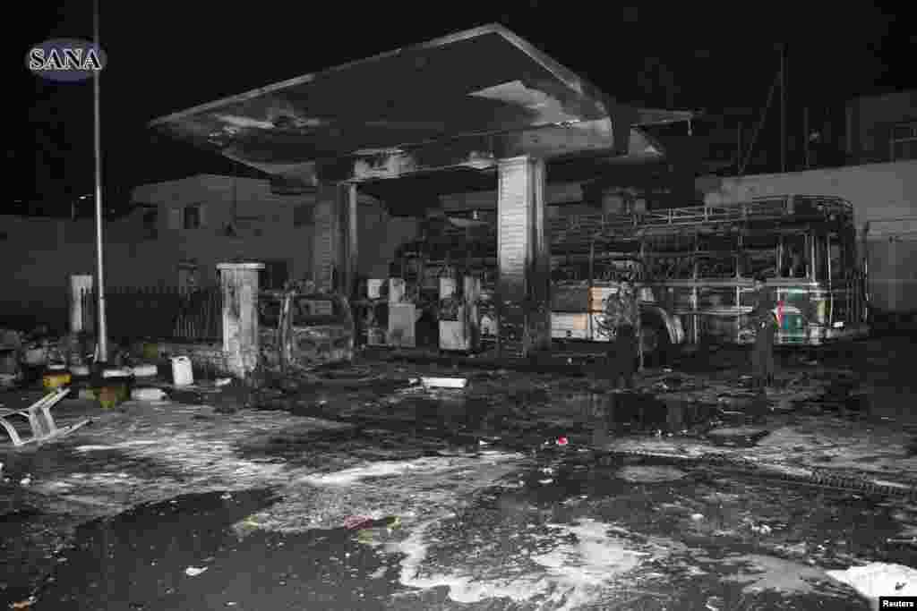 Men stand amidst wreckage and debris after a car bomb exploded at a crowded gas station in Barzeh al-Balad district in Damascus, in this handout photograph released by SANA on January 3, 2013.