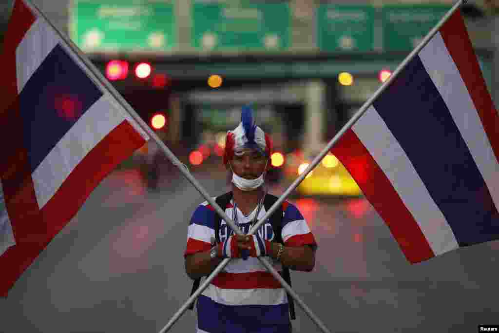 An anti-government protester holds two Thai flags as his group arrives to block one the of the major intersections of the city, Bangkok, Thailand, Jan. 12, 2014.