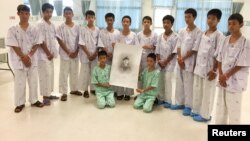 "The 12-member ""Wild Boars"" soccer team and their coach rescued from a flooded cave pose with a drawing picture of Samarn Kunan, a former Thai navy diver who died working to rescue them at the Chiang Rai Prachanukroh Hospital, in Chiang Rai, Thailand, July"