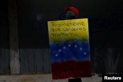 """A demonstrator holding a rudimentary shield that reads """"Promise me you will come back tomorrow. Venezuela"""", poses for a picture before a rally against Venezuelan President Nicolas Maduro's government in Caracas, Venezuela, June 17, 2017."""
