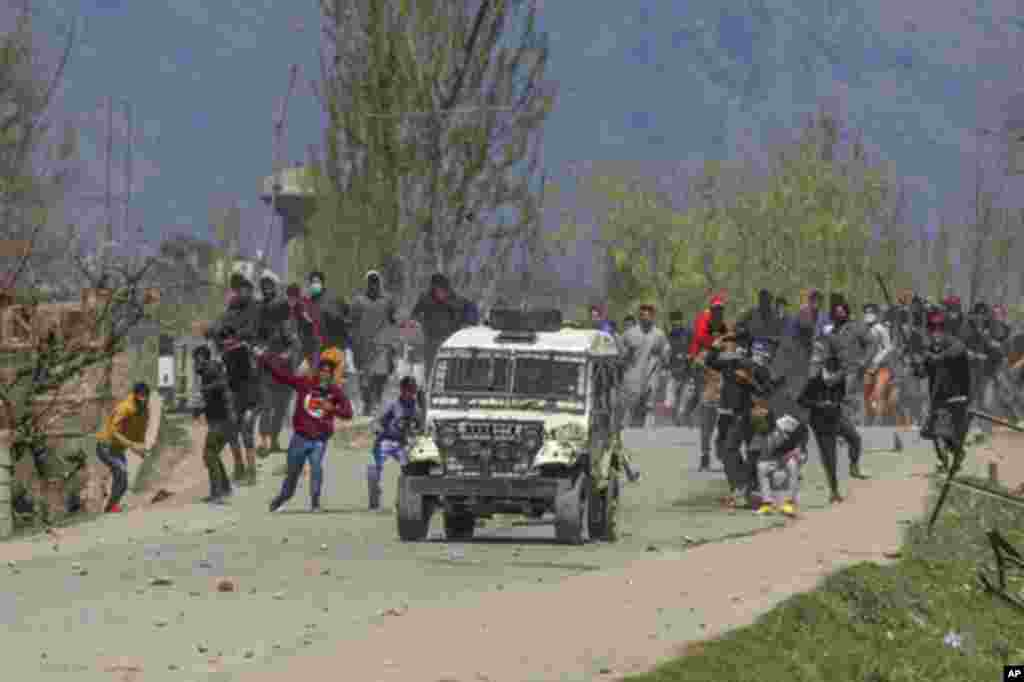 Kashmiri villagers throw stones and bricks at a police vehicle during a protest near the site of a gunbattle in Pulwama, south of Srinagar, Indian-controlled Kashmir.