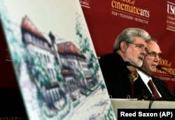 Former University of Southern California student and film director George Lucas, left, and USC president Steven Sample talk with reporters before the ceremonial groundbreaking for a new building at the USC School of Cinematic Arts.