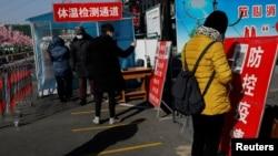 北京市民在进入一个市场前用手机刷健康码。(2021年1月11日)