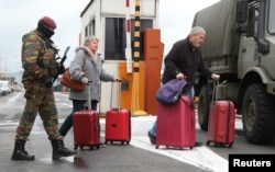 A Belgian soldier accompanies passengers at Brussels' Zaventem airport following Tuesday's bomb attacks in Brussels, March 23, 2016.