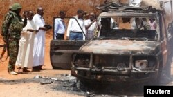 Security officers and government officials inspect a police car that was burnt during an attack on a convoy escorting the governor of Mandera region Ali Roba outside Mandera town, near Kenya's border with Somalia and Ethiopia, March 13, 2015.