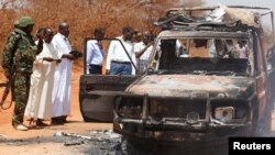FILE - Security officers and government officials inspect a police car that was burnt during an attack on a convoy escorting the governor of Mandera region Ali Roba outside Mandera town, near Kenya's border with Somalia and Ethiopia, March 13, 2015.