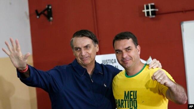 El favorito a la presidencia de Brasil, Jair Bolsonaro (izq.), del Partido Social Liberal y su hijo Flavio saludan a la prensa en un sitio de votación en Río de Janeiro, el 7 de octubre de 2018.