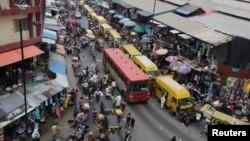 FILE - In this photo taken June 20, 2016, pedestrians shop at a market in Lagos, Nigeria.