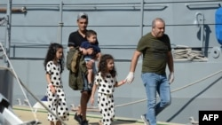 Des personnes d'un groupe de 58 migrants à la base maritime de Hay Wharf à Floriana, à Malte, le 30 septembre 2018.