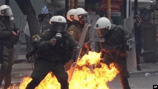 A petrol bomb explodes among riot police during clashes with protesters in Athens, 15 Dec 2010