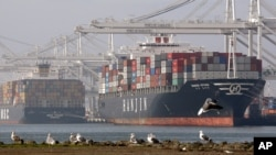 Cargo ships wait to be unloaded Tuesday, Jan. 5, 2010, at the Port of Oakland in Oakland, Calif.
