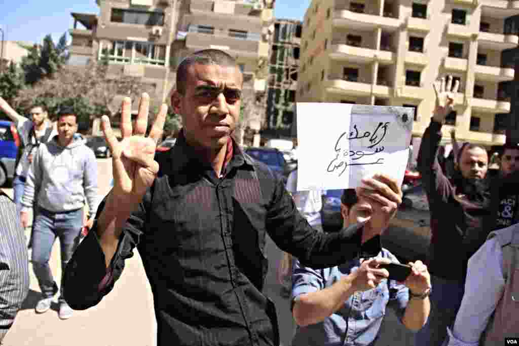 A protester holds up four-fingers, a hand sign in memory of last year's deadly crackdown on supporters of ousted President Mohamed Morsi, Cairo, March 28, 2014. (Hamada Elrassam/VOA)