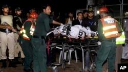 27일 파키스탄 라호르 시의 공원에서 폭탄 테러가 발생한 가운데, 구조요원들이 희생자들의 사체를 옮기고 있다.