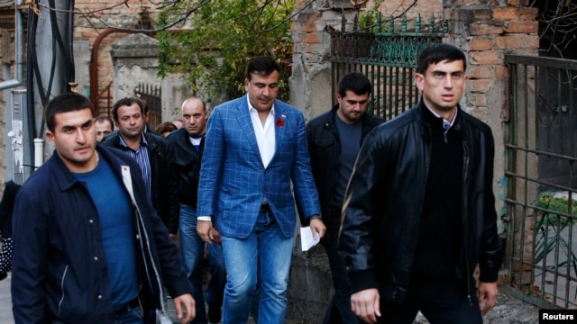 Georgia's outgoing President Mikheil Saakashvili (C) is seen heading to a polling station in Tbilisi October 27, 2013.
