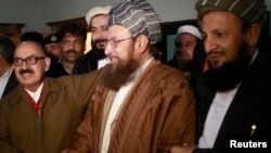 Maulana Sami ul-Haq (front C), one of the Taliban negotiators, and Irfan Siddiqui (front L), a government negotiator, shake hands after a news conference in Islamabad on February 6, 2014.