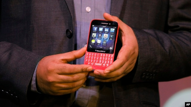 FILE - A BlackBerry official displays a BlackBerry Q5 smartphone during its launch.
