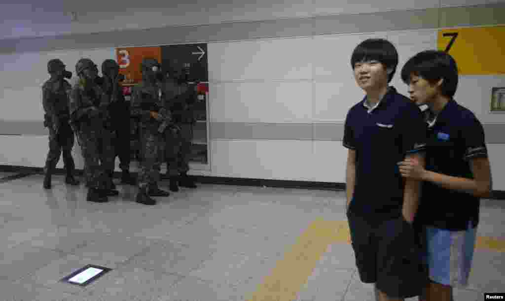 Students walk past South Korean soldiers wearing gas masks during an anti-terror drill at a subway station in Seoul during joint South Korean-U.S. military drills, August 19, 2013.