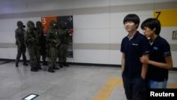 Dua siswa Korea Selatan berjalan melewati tentara (mengenakan masker gas) dalam latihan bersama militer Korea Selatan dan AS di sebuah stasiun kereta bawah tanah di Seoul (19/8).